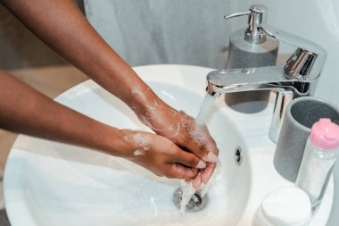 Cropped view of african american woman washing hands in bathroom