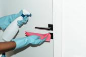 Ausgeschnittene Ansicht einer Afroamerikanerin in Gummihandschuhen, die Türgriff mit Lappen und Spray wischt