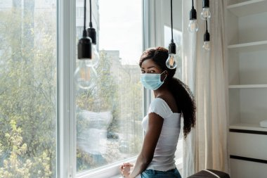 African american woman in medical mask near windows looking at camera in living room stock vector