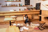 Schockierter Café-Besitzer blickt auf Taschenrechner und sitzt neben Tisch, Papieren und Karte mit Coronavirus-Schriftzug auf dem Boden