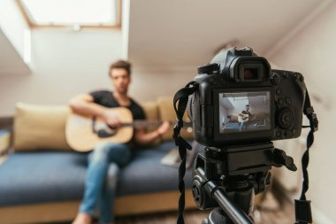 Selective focus of video blogger playing guitar while looking at digital camera stock vector