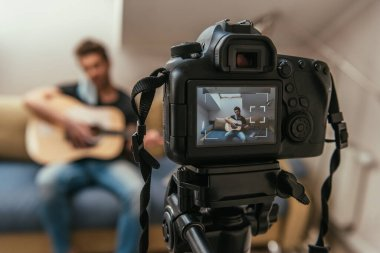 selective focus of young vlogger playing guitar while looking at digital camera