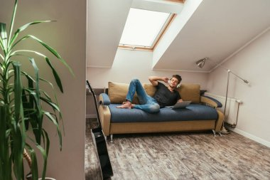 young man listening music in wireless headphones while lying on sofa near laptop in attic room