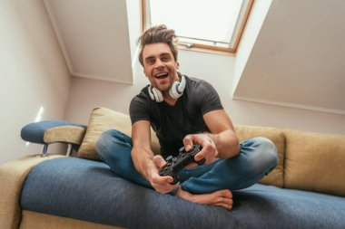 KYIV, UKRAINE - APRIL 13, 2019: low angle view of excited man in wireless headphones on neck playing video game while sitting on sofa stock vector