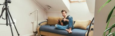 handsome vlogger pointing with finger while knitting on sofa at home in attic room, horizontal image