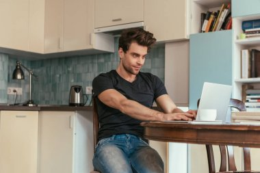 attentive, smiling man typing on laptop in kitchen