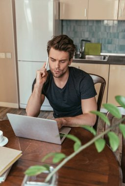 selective focus of serious man talking on smartphone near laptop while working in kitchen