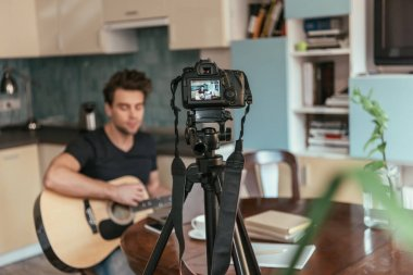 selective focus of young vlogger playing guitar in kitchen near digital camera on tripod