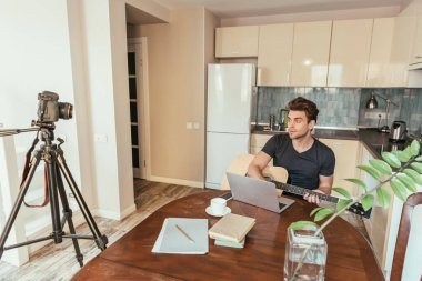 handsome young vlogger playing guitar while looking at digital camera on tripod in kitchen