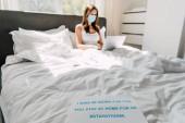 mladý na volné noze v lékařské masce pracující na notebooku v posteli s Stay at home banner během vlastní izolace, selektivní zaměření
