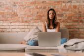samice mladá na volné noze pracuje na notebooku na pohovce během vlastní izolace