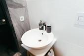 moderní interiér koupelny s bílým umyvadlem a dávkovačem mýdla