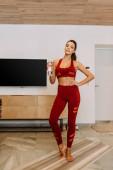 vonzó nő gazdaság sport palack jóga mat otthon elszigetelten