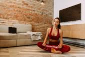 krásná žena školení on-line s notebookem, zatímco sedí s karanténní znamení na podložce jógy doma