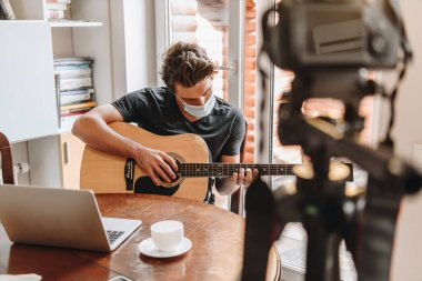 Selective focus of young vlogger in protective mask playing guitar near laptop and digital camera on tripod stock vector