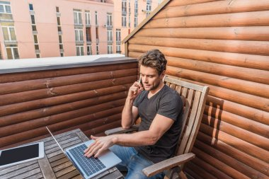 handsome, serious man using laptop and talking on smartphone while sitting on balcony