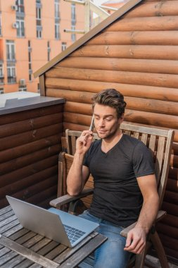 young, skeptical man using laptop and talking on smartphone while sitting on balcony