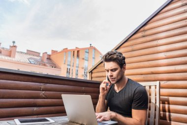 young, serious man using laptop and talking on smartphone while sitting on balcony