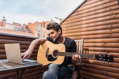 handsome young man holding guitar and using laptop while sitting on balcony