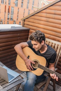 high angle view of young man playing guitar while sitting on balcony and looking at laptop