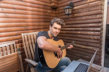 handsome man looking at camera while sitting on balcony near laptop and playing guitar