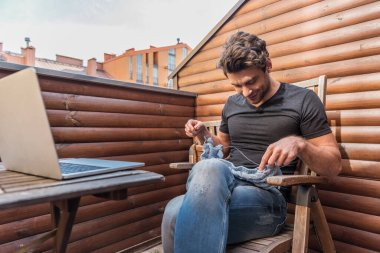 handsome, smiling man knitting while sitting on balcony near laptop