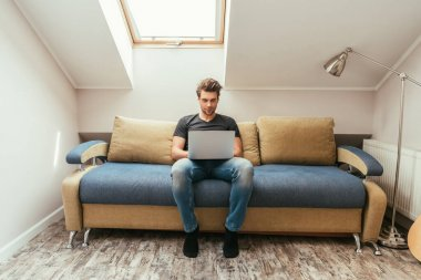 handsome, attentive young man using laptop while sitting on sofa in attic room