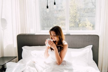 attractive positive girl drinking coffee in bed in morning during self isolation