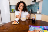 africká americká žena drží lžíci s kukuřičnými vločkami v blízkosti misky, toast chléb, džem a šálek s kávou na stole