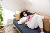 mladá africká americká žena v lékařské masce ležící na pohovce a čtení časopisu