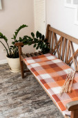 plaid blanket on wooden bench near green plant