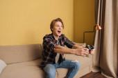 KYIV, UKRAINE - Április 24, 2020: boldog ember kezében joystick játék közben a nappaliban