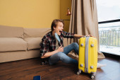 vzrušený muž v lékařské masce sedící na podlaze a dívající se na zavazadla, koncept konce karantény