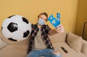 selektivní zaměření člověka v lékařské masce držícího lístky na fotbal a sportovní utkání, konec koncepce karantény