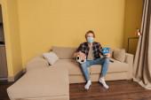 Überraschter Mann mit medizinischer Maske hält Fußball- und Sportspielkarten in der Hand, während er zu Hause die Meisterschaft verfolgt