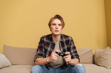 KYIV, UKRAINE - APRIL 24, 2020: handsome man holding joystick while playing video game in living room stock vector