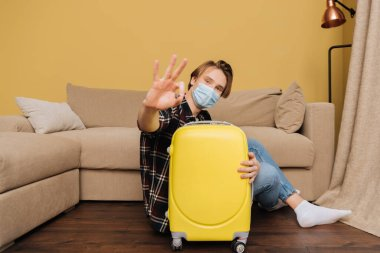Selective focus of man in medical mask sitting on floor near baggage and showing ok sign, end of quarantine concept stock vector