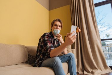 Shocked man in medical mask looking at smartphone in living room stock vector