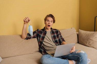 Shocked freelancer holding medical mask near laptop in living room, end of quarantine concept stock vector