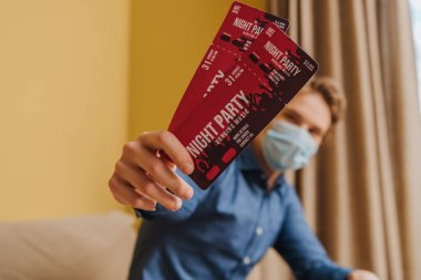 Selective focus of man in medical mask holding night party tickets, end of quarantine concept stock vector