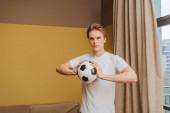 pohledný muž drží fotbal doma, konec karantény koncept