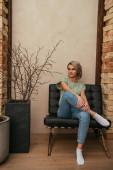 krásná mladá žena dívá pryč, zatímco sedí v křesle doma