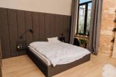 prostorná ložnice s velkou postelí, tmavé záclony na okně a květináče na parapetu
