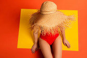 felső kilátás fiatal nő fürdőruhában és szalma kalap narancs