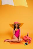 vonzó lány szalma kalap és fürdőruha tartó üveg narancslé közelében felfújható gyűrű és vízipisztoly sárga