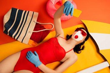 Girl in sunglasses, medical mask, latex gloves and swimsuit taking selfie near bag on orange stock vector