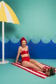 veselá žena v červeném ručníku a plavky sedí v blízkosti modrého papíru střih vlny