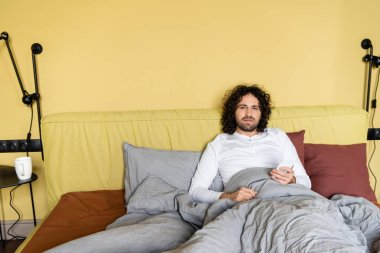 Serious, curly man looking at camera while chatting on smartphone in bed stock vector