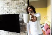selektiver Fokus eines gutaussehenden Mannes mit Kaffeetasse in ausgestreckter Hand in der Nähe eines leeren LCD-Bildschirms, der an der Ziegelwand hängt
