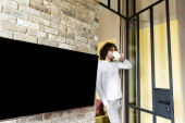 young man in pajamas drinking coffee while standing near blank lcd screen hanging on brick wall